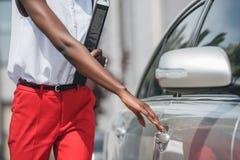 imagem colhida da porta afro-americano à moda do táxi da abertura da mulher de negócios na rua imagens de stock