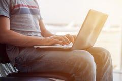 Imagem colhida de um homem que usa o portátil para escrever email no terminal de aeroporto Fotografia de Stock Royalty Free
