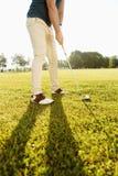 Imagem colhida de um jogador de golfe que põe a bola de golfe sobre o verde Imagem de Stock Royalty Free