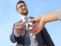 Imagem colhida do agente imobiliário que dá chaves da casa ao homem no escritório Imagens de Stock