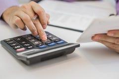 Imagem colhida do ancião considerável que usa uma calculadora e escrevendo em seu caderno ao trabalhar em casa Foto de Stock