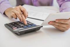 Imagem colhida do ancião considerável que usa uma calculadora e escrevendo em seu caderno ao trabalhar em casa Fotografia de Stock Royalty Free
