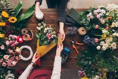 imagem colhida do cliente que dá o cartão de crédito do florista ao pagamento fotografia de stock royalty free
