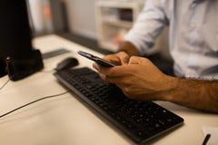 Imagem colhida do homem de negócios que usa o telefone celular ao sentar-se na mesa fotografia de stock