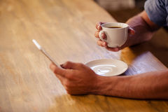 Imagem colhida do homem do moderno que usa o smartphone ao beber a xícara de café imagem de stock royalty free