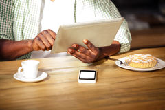 Imagem colhida do homem do moderno que usa a tabuleta ao comer e ao beber imagem de stock