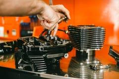 Imagem colhida do mecânico de automóvel que repara a motocicleta imagens de stock