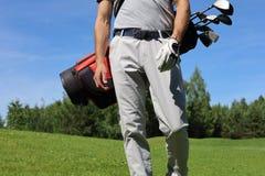 Imagem colhida do saco de golfe levando do jogador de golfe masculino com motoristas ao andar pela grama verde fotografia de stock