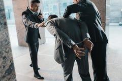 Imagem colhida dos agentes de segurança que prendem o delinquente e a fala fotos de stock royalty free