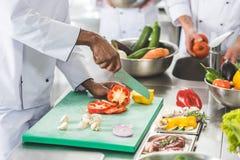 imagem colhida dos cozinheiros chefe multiculturais que cortam e que lavam vegetais imagem de stock royalty free