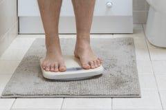 A imagem colhida dos pés do homem que estão sobre pesa a escala foto de stock royalty free