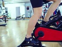Imagem colhida dos pés do homem saudável novo que exercita na máquina da bicicleta no gym do esporte Conceito da aptidão e do exe foto de stock