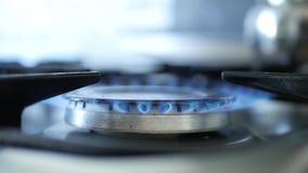 Imagem com o fogão do fogão que queima-se com a chama azul do fogo de gás da cor filme