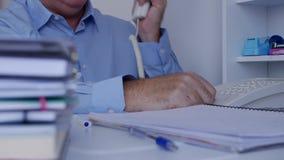 Imagem com o homem de negócios no escritório que faz um telefonema usando a conexão da linha terrestre filme