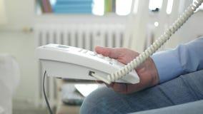 Imagem com o homem que senta-se em uma cadeira na sala do escritório usando a conexão da linha terrestre do telefone vídeos de arquivo