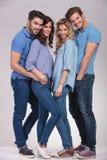 Imagem completa do corpo de quatro povos ocasionais felizes que estão junto Fotografia de Stock Royalty Free