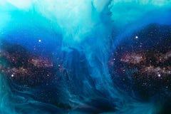 A imagem completa do quadro de misturar a pintura azul espirra na água com o fundo do universo imagens de stock