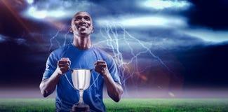 Imagem composta 3D do atleta feliz que guarda o troféu que olha acima Fotos de Stock Royalty Free