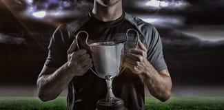 Imagem composta 3D do jogador vitorioso do rugby que guarda o troféu Foto de Stock Royalty Free