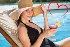 Imagem composta da bebida bonita da terra arrendada da mulher pela piscina Fotografia de Stock