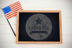 A imagem composta da imagem composta digital de comemora o texto do Dia do Trabalhador com a bandeira americana no po azul Fotografia de Stock