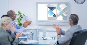 Imagem composta da equipe do negócio que aplaude e que olha a tela branca foto de stock royalty free