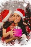 Imagem composta da filha que dá a sua mãe um presente de Natal Foto de Stock