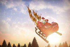 Imagem composta da ideia de ângulo alto da equitação de Papai Noel no trenó com caixa de presente Fotos de Stock Royalty Free