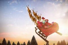 Imagem composta da ideia de ângulo alto da equitação de Papai Noel no trenó com caixa de presente Fotografia de Stock Royalty Free