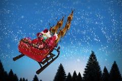 Imagem composta da ideia de ângulo alto da equitação de Papai Noel no trenó com caixa de presente Imagens de Stock