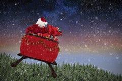 Imagem composta da ideia traseira da equitação de Papai Noel no trenó com caixa de presente Imagens de Stock Royalty Free