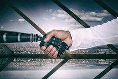 Imagem composta da imagem composta digital do homem de negócios e do robô que agitam as mãos Imagens de Stock