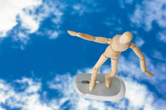 Imagem composta da imagem 3d da estatueta de madeira despreocupada que está no rato do computador Imagem de Stock