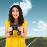 Imagem composta da jovem mulher ocasional de sorriso que guarda binóculos Foto de Stock