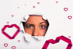 Imagem composta da jovem mulher que olha através do rasgo de papel Fotos de Stock