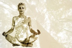 Imagem composta da jovem mulher tonificada que senta-se na pose dos lótus com os olhos fechados Fotografia de Stock Royalty Free