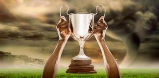 Imagem composta da mão colhida do atleta que guarda o troféu 3D Foto de Stock