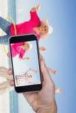 Imagem composta da mão que mantém o telefone celular contra o fundo branco imagem de stock