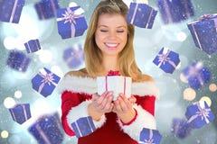 Imagem composta da menina bonita no equipamento de Santa que guarda o presente Foto de Stock Royalty Free