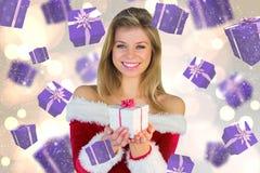Imagem composta da menina bonita no equipamento de Santa que guarda o presente Imagens de Stock Royalty Free