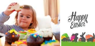 Imagem composta da menina feliz que come confeitos em casa foto de stock