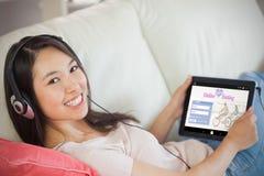 Imagem composta da menina que usa seu PC da tabuleta no sofá e escutando a música que sorri na câmera imagem de stock royalty free