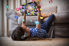 Imagem composta da menina que usa a tabuleta digital na sala de visitas 3d Fotografia de Stock Royalty Free