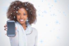 Imagem composta da mulher com o afro que mostra seu smartphone imagens de stock royalty free