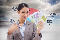 Imagem composta da mulher de negócios de sorriso que guarda cédulas imagens de stock royalty free
