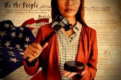 Imagem composta da mulher de negócios que golpeia um martelo da lei no martelo fotografia de stock royalty free