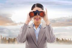 Imagem composta da mulher de negócios que olha através dos binóculos imagem de stock