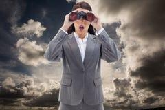 Imagem composta da mulher de negócios surpreendida que olha através dos binóculos Fotografia de Stock