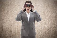 Imagem composta da mulher de negócios surpreendida que olha através dos binóculos Foto de Stock