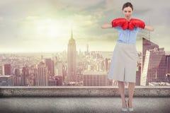 Imagem composta da mulher de negócios resistente que levanta com as luvas de encaixotamento vermelhas Imagens de Stock
